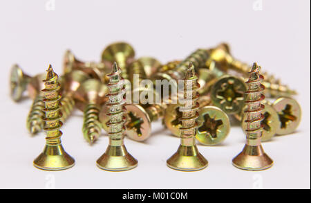 Bunch of yellow zinc coated philips flat head cross screws - fasteners on a white background - Stock Photo