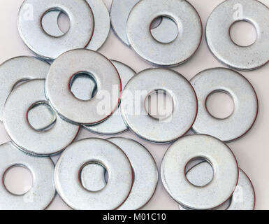 Pile of flat metal washers for screws and fasteners - Stock Photo