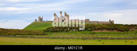 English medieval castle Dunstanburgh Northumberland England uk panoramic view - Stock Photo