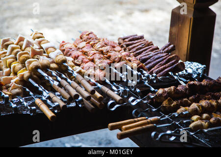 Many skewers with raw pork and veal meat and raw potatoes with bacon. Next to it there is a skewer with sausages - Stock Photo