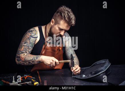 Artist working with leather works with leather goods./Leather workman producing a leatherwork at his workshop. - Stock Photo