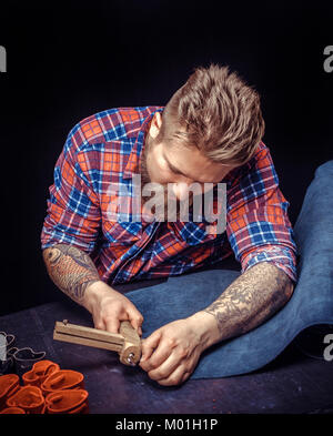 Leather Artist performing leatherwork on a new product piece at his workshelf./Leather Tanner keen on one's business - Stock Photo