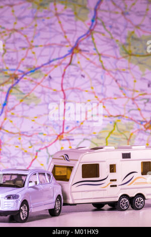Model caravan and car with a defocused map / atlas in the background. Concept of any aspect of camping / touring / freedom of the open road, etc.