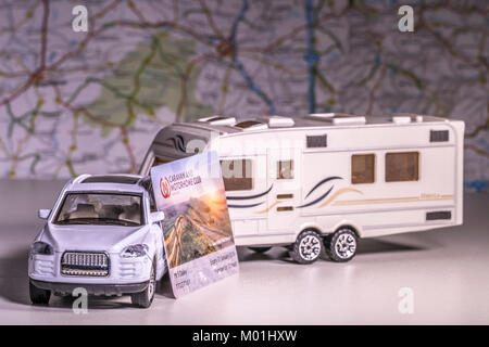 Model caravan and car with UK 'Caravan and Motorhome Club' membership card and defocused map / atlas. Concept of touring using a campsite network.