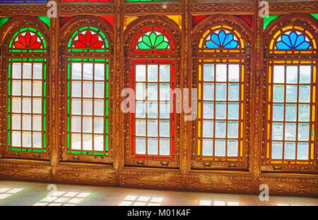 SHIRAZ, IRAN - OCTOBER 12, 2017: The medieval stained glass windows with colored glasses and wooden frames, covered - Stock Photo