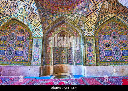 SHIRAZ, IRAN - OCTOBER 12, 2017: The tiled mihrab in Nasir Ol-Molk mosque with fine patterns and muqarnas details, - Stock Photo