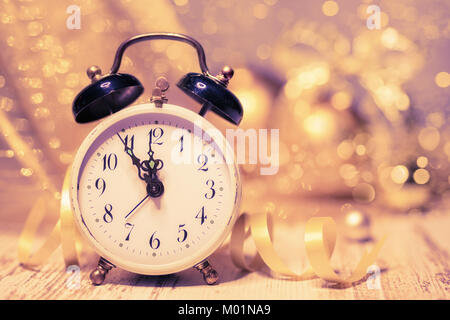 Greeting card design 'Happy New Year!' with vintage alarm clock showing five to midnight on abstract glitter background. Space for your text. Shallow