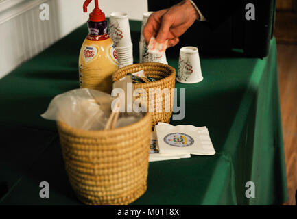 An attendee of the Federal Executive Association holiday coffee drop-in prepares coffee Dec. 15, 2017, at Coast - Stock Photo
