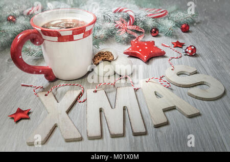 Wooden letters 'Xmas', cup of steaming tea and winter decorations in red and dark green. Merry Christmas! - Stock Photo