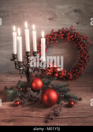 Greeting card 'Merry Christmas!' with decorations in red and green on wooden table. This image is toned. Focus on - Stock Photo