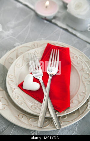 Table setting (two forks) for Valentine\'s Day with red hearts on ...