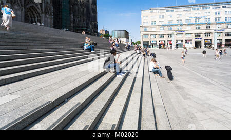 COLOGNE, GERMANY - JUNE 27, 2010: tourists on steps in front of Cologne Cathedral on Bahnhofsvorplatz. The Cathedral - Stock Photo