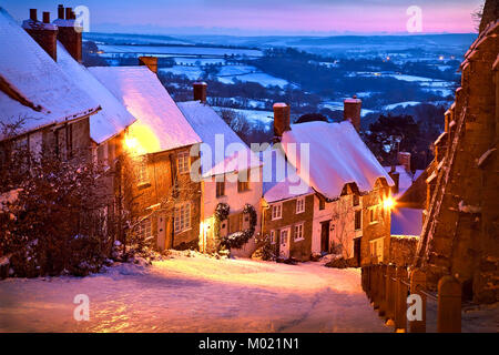 Gold Hill Shaftesbury Dorset after a fall of snow and lit by an evening sunset on a cold January winters evening - Stock Photo