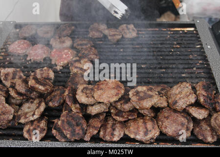 Fresh meatballs, sausage and hot dogs grilled outdoors on a gas grill. Meatballs on a barbecue.Homemade meatballs - Stock Photo