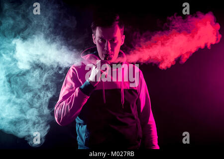 Portrait of a young handsome man who breathes out a large cloud  red and blue smoke on a dark background - Stock Photo