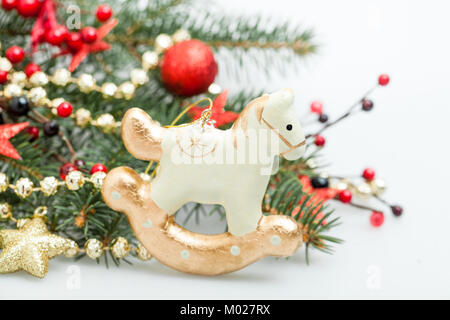 Christmas Decor on New Year Background of Xmas Tree Twig, Red Glass Ball, Garland and Ribbon - Stock Photo