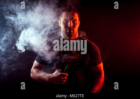 A young stylish man smoker in a black T-shirt is holding a    vape in his hand, and around and a big cloud of smoke - Stock Photo