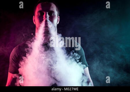 A young stylish male smoker in a black T-shirt exhales a large cloud of smoke from vape on a black isolated background - Stock Photo