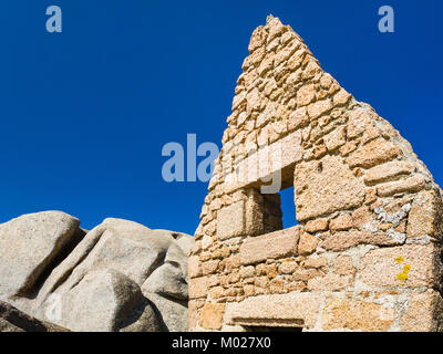 travel to France - facade of old ruined breton stone house in Ploumanac'h site of Perros-Guirec commune on Pink - Stock Photo