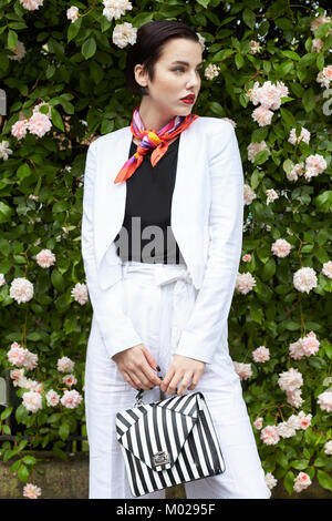 Woman in white linen culotte suit standing by flowering bush - Stock Photo