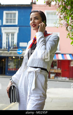 Woman in white linen culotte suit using phone in street - Stock Photo