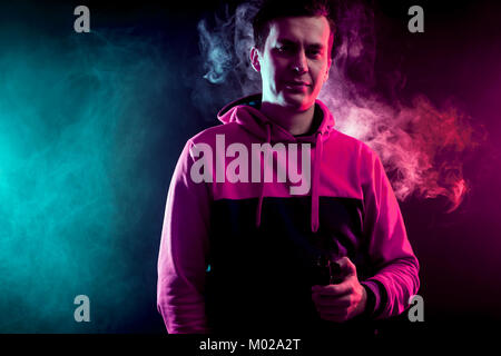 Man in sport hoody vaping an electronic cigarette.Isolated on black background.Around pink and green clouds of smoke - Stock Photo