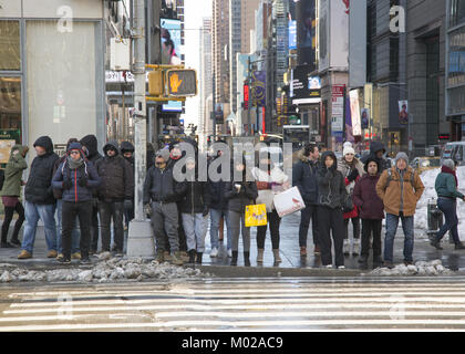 People bundled up on a cold winter day in midtown Manhattan wait to cross 6th Avenue on 42nd Street by Bryant Park. - Stock Photo