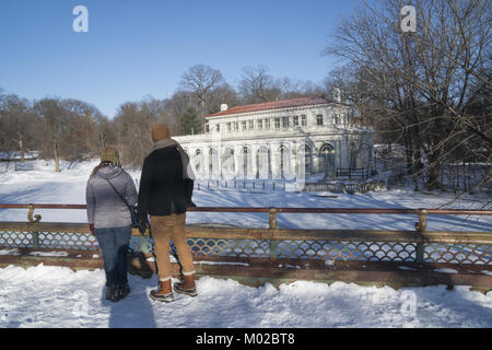 Couple look out from the Lullwater Bridge at the iconic Boathouse building after a snow  in Prospect Park, Brooklyn, - Stock Photo