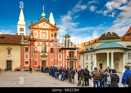Tourists and visitors queue to enter St. George's Basilica within the complex of Prague Castle - Stock Photo