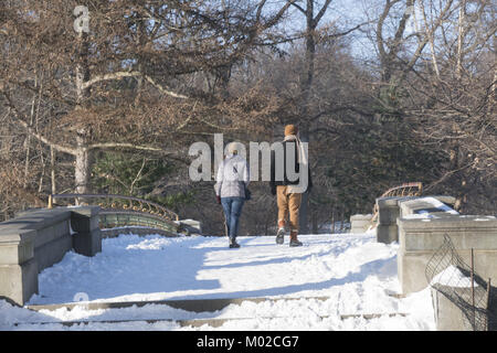 Couple walks over the Lullwater Bridge near the Boathouse in Prospect Park, Brooklyn, NY. - Stock Photo