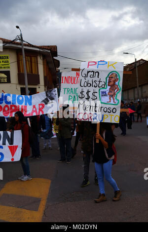 A protester carries a placard accusing Peruvian President Kuczynski of corruption during a protest march, Cusco, - Stock Photo