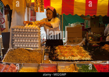 31.12.2017, Tokyo, Japan, Asia - A woman prepares freshly roasted pancakes at a street stall in Tokyo's city district - Stock Photo