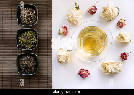 Glass cup of green tea with dry roses around and mat with different kinds of green tea. China's concept. Top view. - Stock Photo