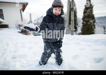 Laughing child in warm clothes having fun during a snowball fight. Boy having fun in the snow. - Stock Photo