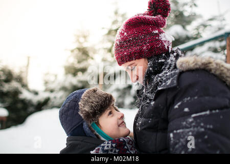 Side view of a happy mother and her son looking into each other's eyes after a snowball fight - Stock Photo