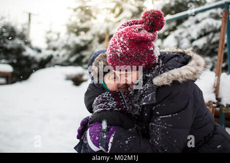 Side view of a happy mother and her son hugging each other after a snowball fight. Family having fun in the snow. - Stock Photo