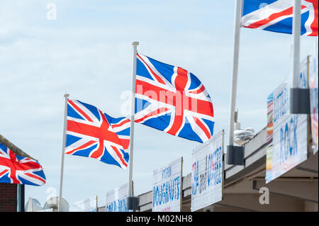 Union Jack flags flying over fast food signs and against a blue sky on a summers day on the seafront in Littlehampton, - Stock Photo