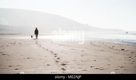 Walking on Croyde Beach with dog in winter - Stock Photo