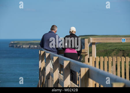 Cliff-top view for couple of people (birdwatchers) standing on viewing platform on sunny day - Bempton Cliffs RSPB - Stock Photo