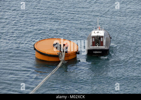 Man casting off mooring ropes to release cruise liner - Stock Photo