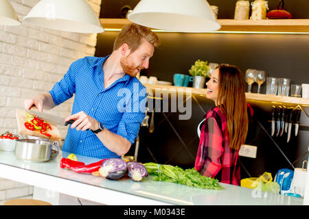 Lovely young couple preparing healthy meal in the modern kitchen - Stock Photo