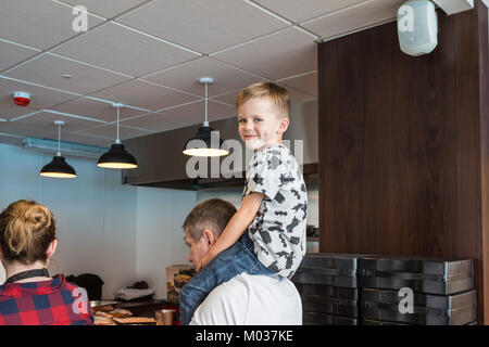 Young boy sitting on fathers shoulders during cooking demonstration - Stock Photo