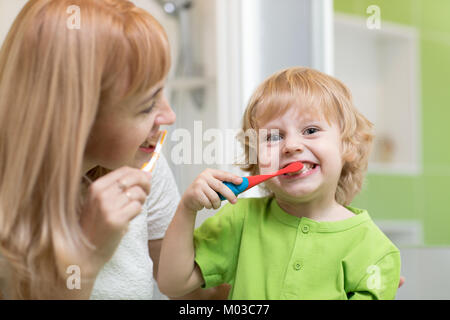 Mother teaches her child son how to brush teeth - Stock Photo