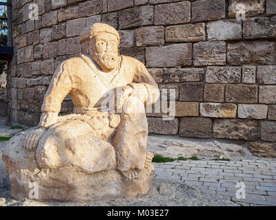 Ancient sculpture of a man at the foot of the Maiden Tower in Old Town in Baku, Azerbaijan. - Stock Photo