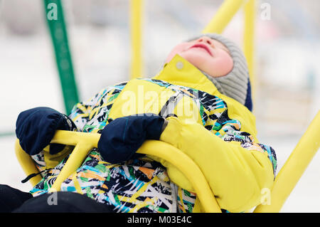 The child. boy in winter clothes riding on a swing, emotion, laughing, winter, snow - Stock Photo