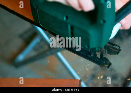 carpenter working with a jig saw and wood cutting jigsaw manual - Stock Photo