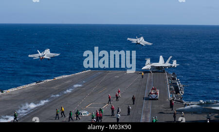 Two F/A-18E Super Hornets from the Kestrels of Strike Fighter Squadron (VFA) 137 take off from the flight deck of - Stock Photo