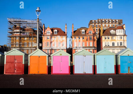 Brighton seafront 7 multi beach huts, behind is blue sky and three very ornate victorian buildings one of the buildings - Stock Photo