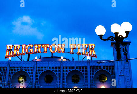 Brighton Pier bright red and yellow neon sign saying Brighton Pier, ontop of Brighton Pier entrance with a street - Stock Photo