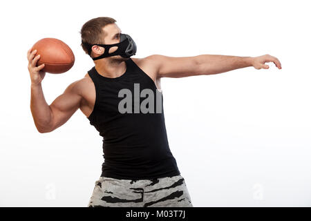 A young male athlete in a black training mask, a sports shirt swings by an  rugby ball on a white isolated background - Stock Photo